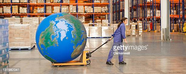 Woman worker pulling large blue ball on hand truck in warehouse