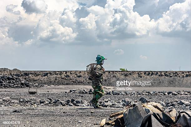 A woman worker who picks up coal from slag back to home after work on a hill which made by mineral waste residue from 1955 in July 04 Fuxin Liaoning...