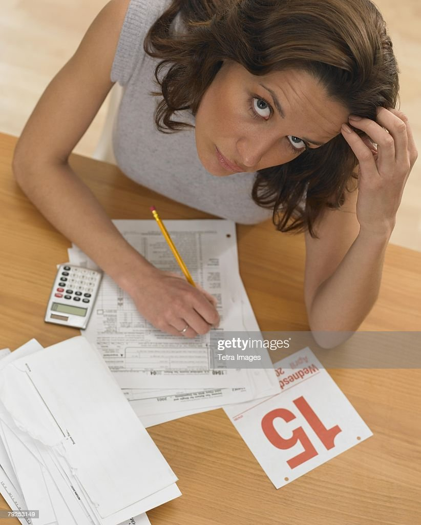 Woman working against tax deadline : Stock Photo