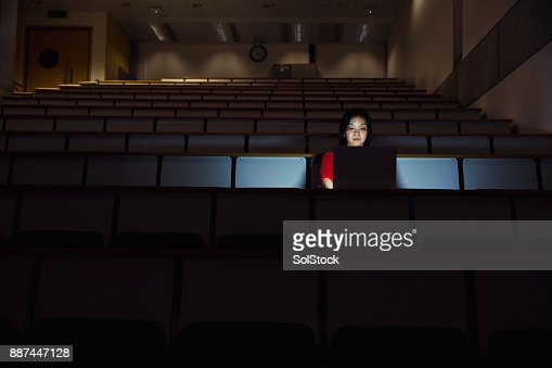 Woman Working Alone in a Seminar Room in the Dark