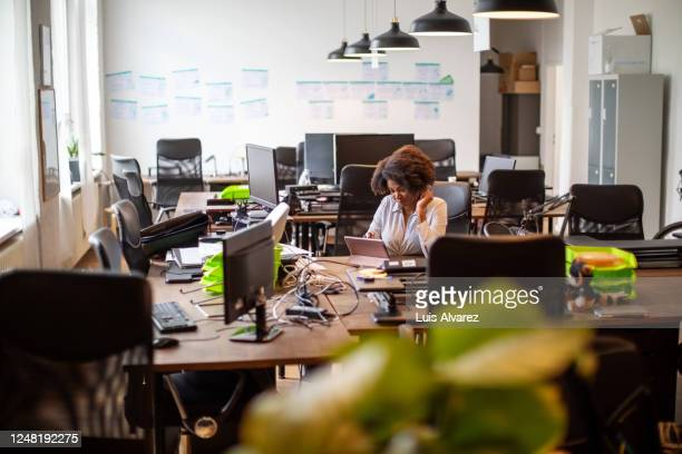 woman working alone in office post covid-19 lockdown - focus on background stock pictures, royalty-free photos & images