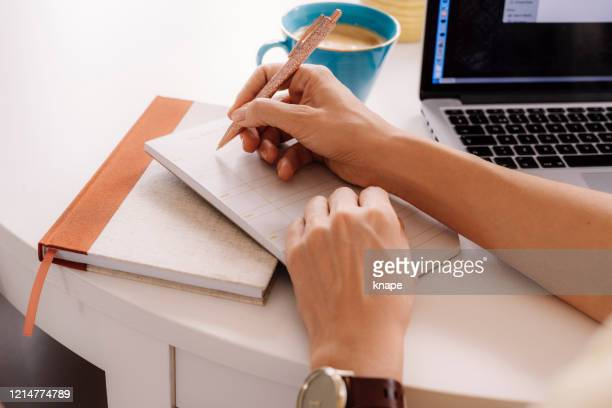 woman working and planning her week hand notes and pen - week stock pictures, royalty-free photos & images