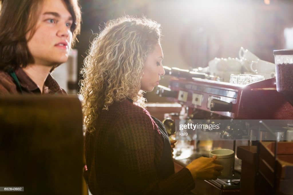 Woman working as barista at coffee shop, with coworker : Stock Photo