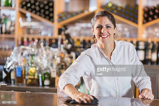 Woman working as bartender, behind the counter