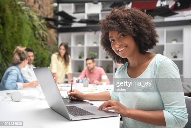 Woman working at a creative office using a laptop computer