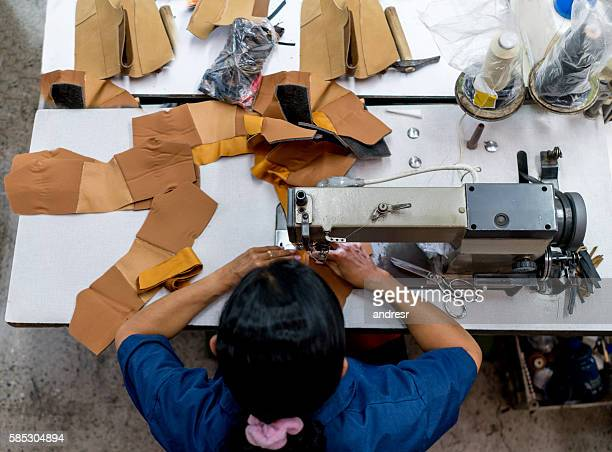 woman working at a factory making shoes - calzature di pelle foto e immagini stock