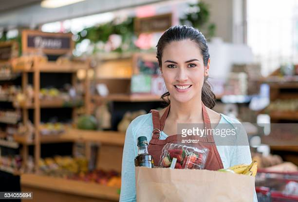 Woman working at a food market holding groceries