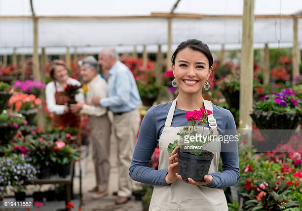 Woman working at a greenhouse selling plants