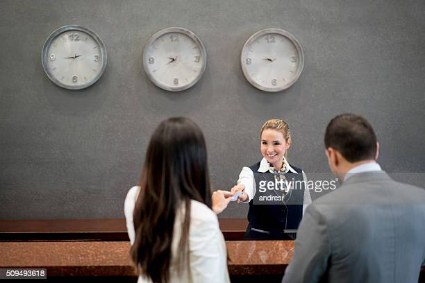woman working at a hotel doing the check in - hotel stock-fotos und bilder