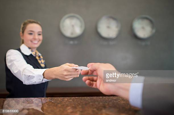 Woman working at a hotel handing a loyalty card
