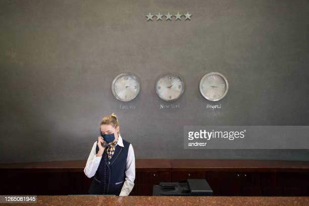 woman working at a hotel's reception wearing a facemask - opening event stock pictures, royalty-free photos & images
