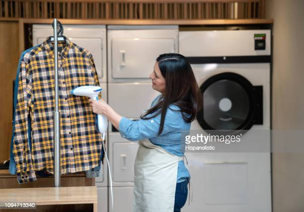 woman working at a laundry service using a garmet steamer on shirt - remove clothes from stock pictures, royalty-free photos & images