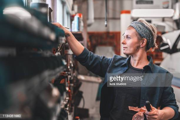 woman working at a repair shop - stereotypically working class stock pictures, royalty-free photos & images