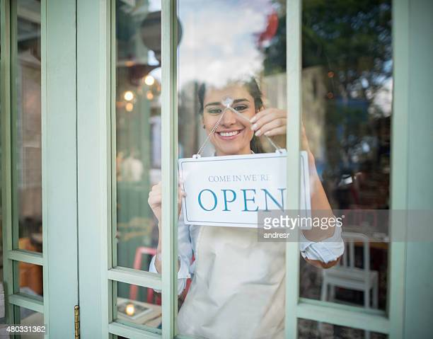 Woman working at a restaurant hanging an open sign