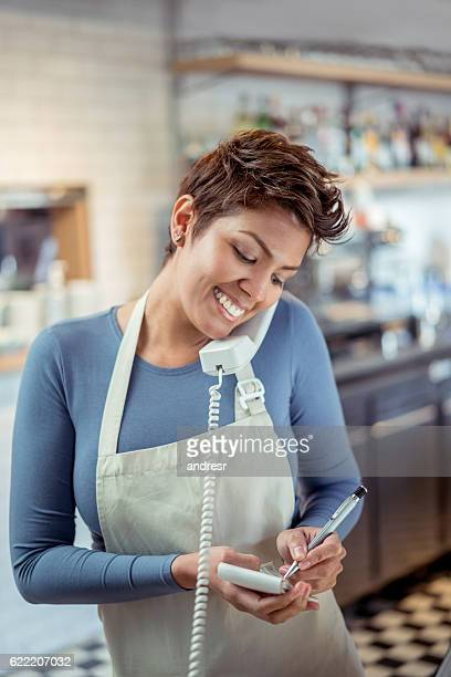 Woman working at a restaurant talking on the phone