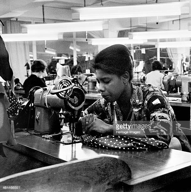 Woman working at a sewing machine, London, . An Afro-Caribbean woman from Grenada at work in a clothing factory.
