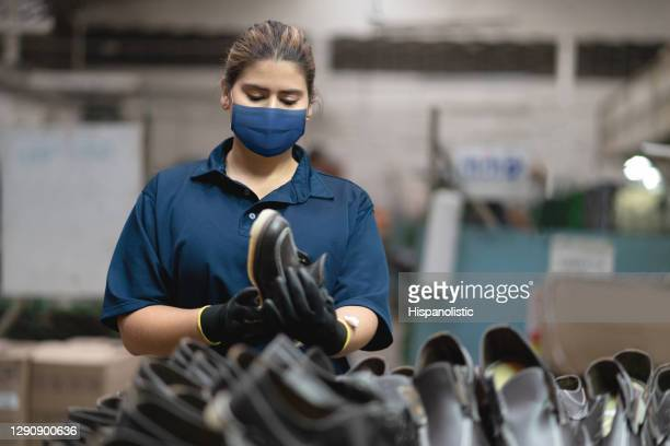 woman working at a shoe factory wearing a facemask - shoe factory stock pictures, royalty-free photos & images