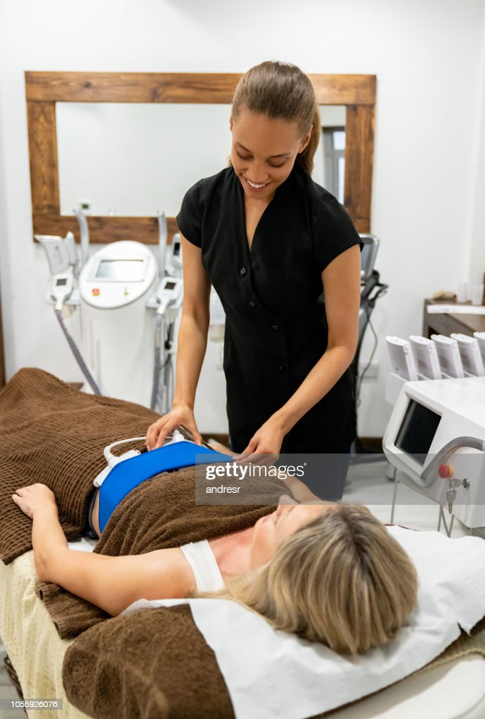 Woman working at a spa doing a fat freezing massage : Stock Photo
