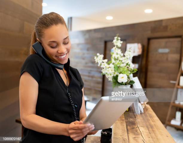 woman working at a spa talking on the phone - spa treatment stock pictures, royalty-free photos & images