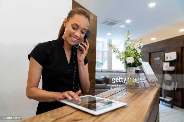 woman working at a spa talking on the phone - hotel stock pictures, royalty-free photos & images