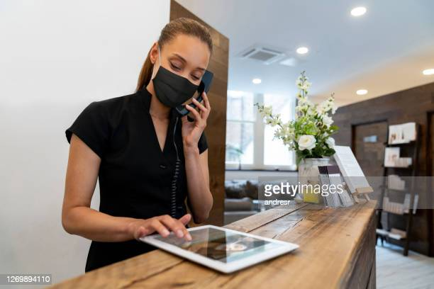 woman working at a spa wearing a facemask while talking on the phone - beauty spa stock pictures, royalty-free photos & images