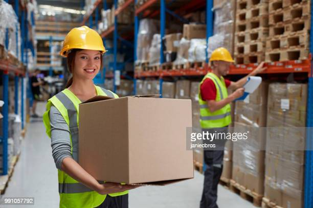 Woman working at a warehouse. Carrying boxes