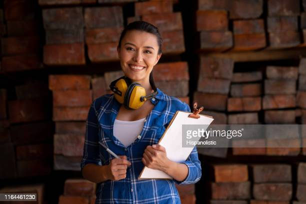 Woman working at a wood factory doing the inventory