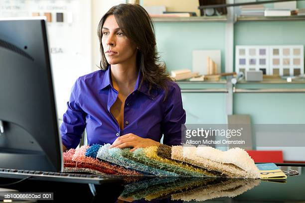 Woman working at computer with pile of carpet samples in office