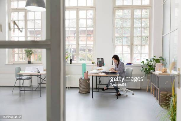 woman working at desk in a loft office - escritorio fotografías e imágenes de stock