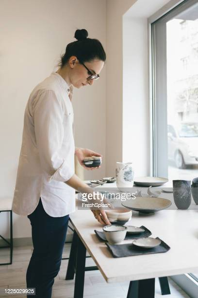 woman working at gallery arranging pottery pieces - art dealer stock pictures, royalty-free photos & images
