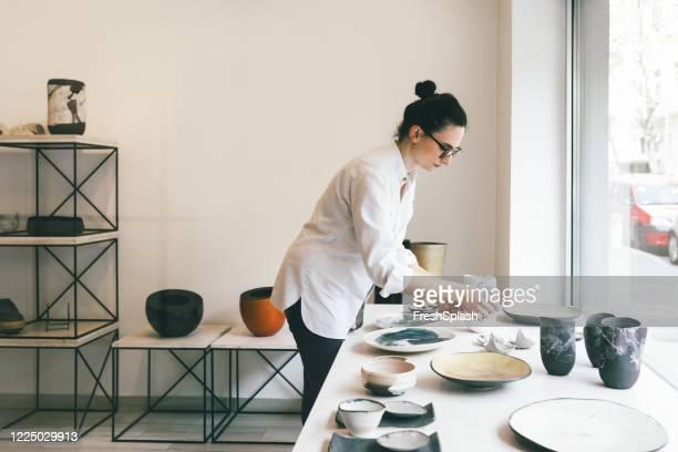 frau arbeitet in der galerie verkauf handgemachte keramik - kunsthändler stock-fotos und bilder