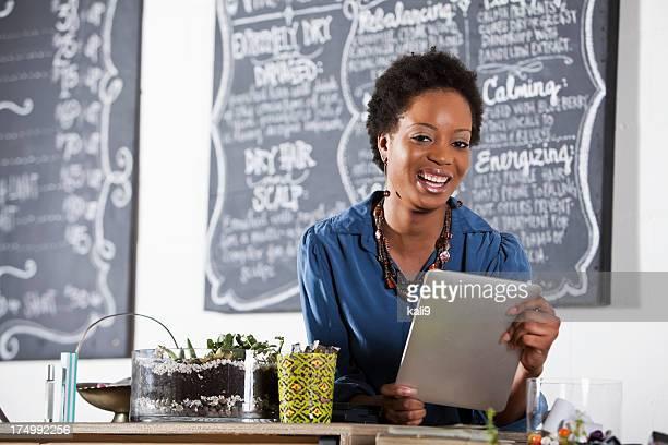 Woman working at hair salon, using digital tablet