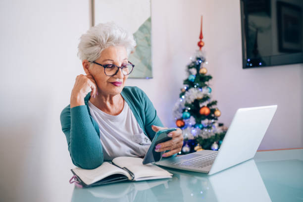 Woman working at home, Christmas tree in background