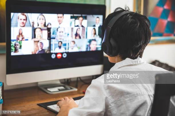woman working at home having a video conference with colleagues - video still stock pictures, royalty-free photos & images