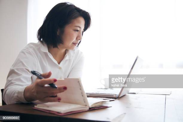 woman working at home - agenda stock pictures, royalty-free photos & images