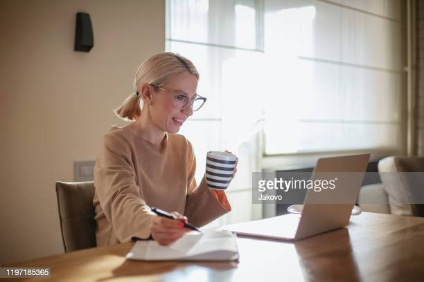 woman working at home while having breakfast - authors stock pictures, royalty-free photos & images