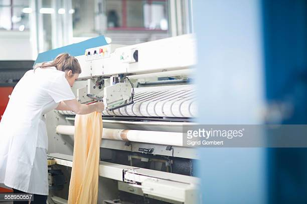 woman working at machinery in laundry - sigrid gombert imagens e fotografias de stock