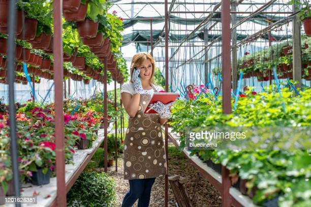 woman working at plant nursery - incidental people stock pictures, royalty-free photos & images