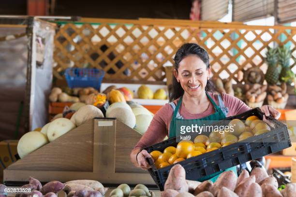 Woman working at produce stand with crate of oranges