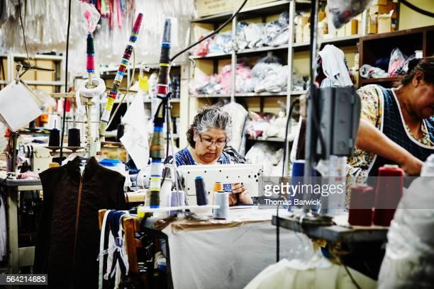 woman working at sewing machine in garment factory - fábrica têxtil imagens e fotografias de stock