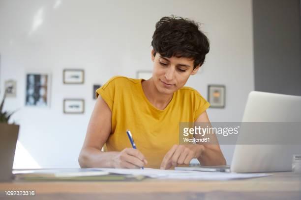 woman working at table at home - schreiben stock-fotos und bilder