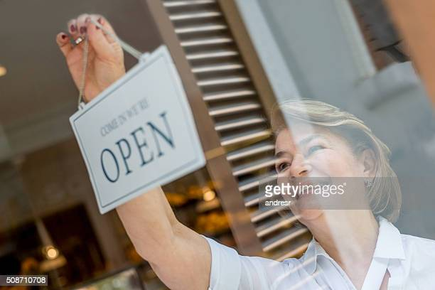 Woman working at the bakery hanging an open sign