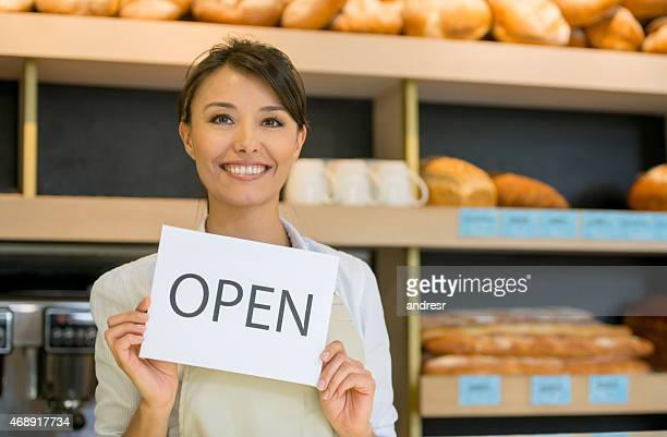 Woman working at the bakery holding an open sign