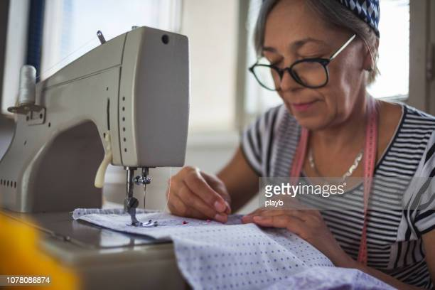 senior woman working at sewing machine