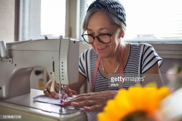 senior woman working at sewing machine