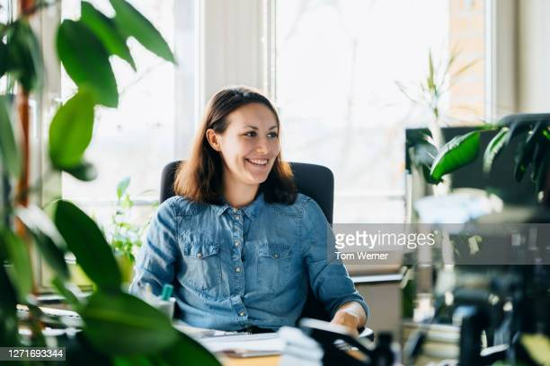 woman working ay desk in modern office space - shirt stock pictures, royalty-free photos & images