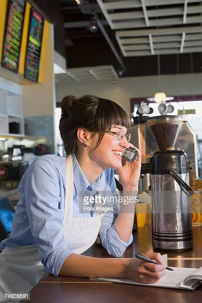 Woman working behind counter at cafe