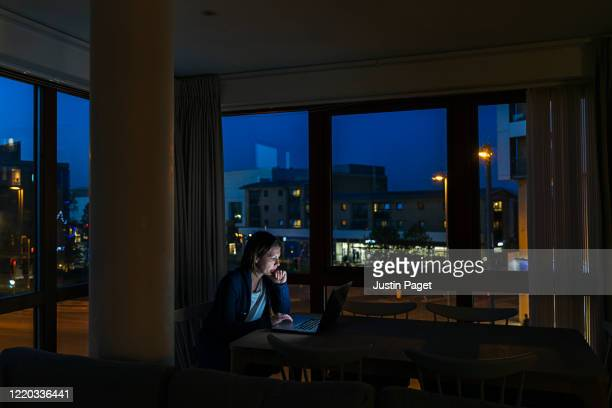 woman working from home at night - working late stock pictures, royalty-free photos & images