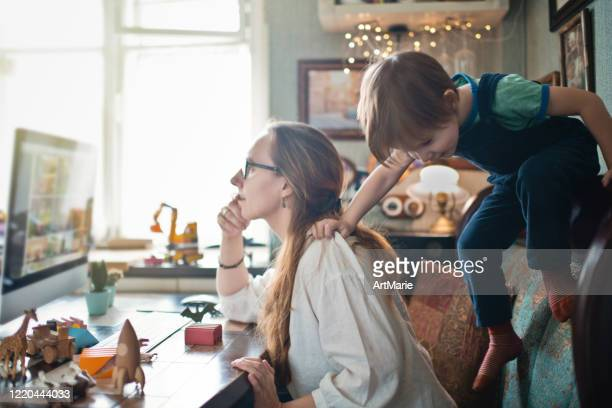 woman working from home during quarantine with her little son all around - tired stock pictures, royalty-free photos & images