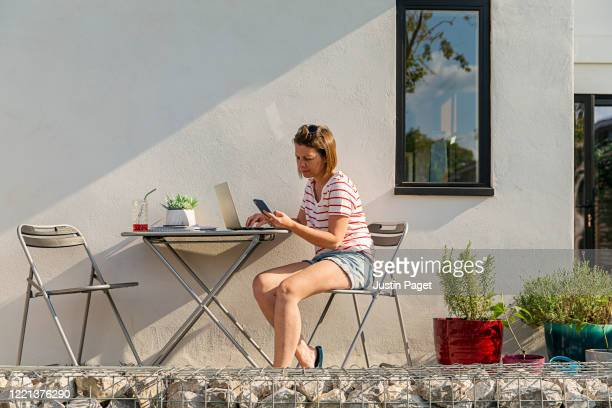 woman working from home garden - sunlight stock pictures, royalty-free photos & images